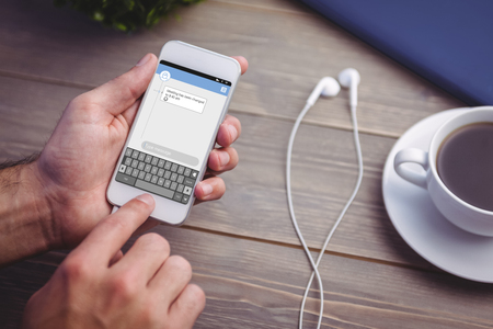 text messaging: Smartphone text messaging  against person holding smart phone at desk
