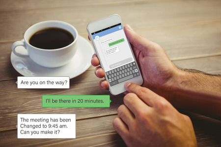 Smartphone text messaging  against person holding smartphone Imagens