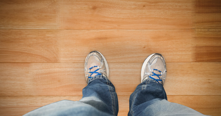 casually dressed: Casually dressed mans feet against wooden flooring