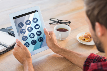 man rear view: Rear view of man using tablet on wooden table against telephone apps icons