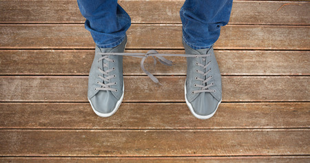tied together: Low section of man with shoelaces tied together  against wooden planks background Stock Photo