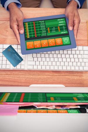 World credit card against businessman holding digital tablet by keyboard at desk Stock Photo
