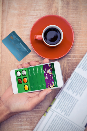 smart card: World credit card against overhead view of person using smart phone by coffee Stock Photo