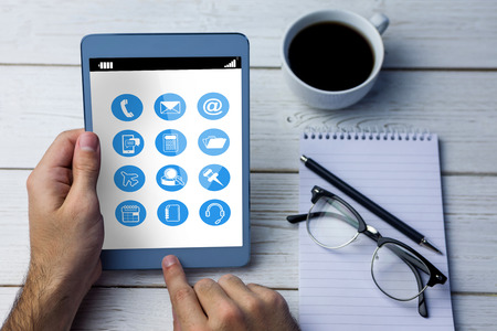 cropped: Telephone apps icons  against cropped image of person using tablet computer