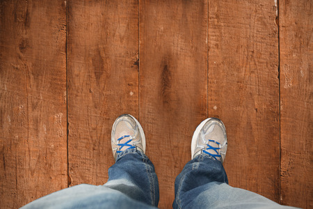 casually dressed: Casually dressed mans feet against wooden planks