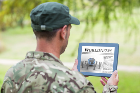 military press: Army man using tablet against international newspaper