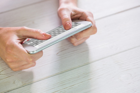 text messaging: Woman using smartphone against smartphone text messaging Stock Photo