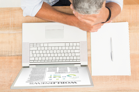 exhausted: International newspaperagainst exhausted casual businessman leaning on wooden desk