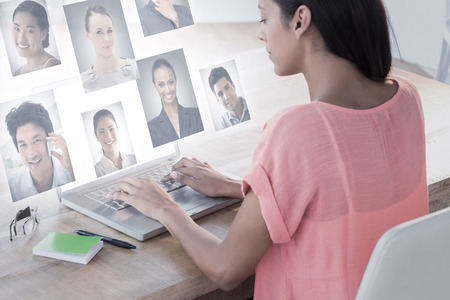 corporate women: Businesswoman using laptop at desk in creative office against profile pictures