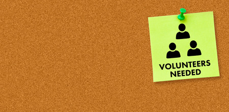 needed: Volunteers needed against digital image of pushpin on green paper Stock Photo