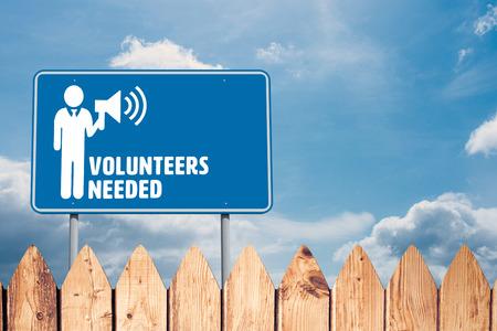 needed: Volunteers needed against fence under blue sky Stock Photo