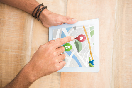 representations: Colorful navigation pointers with various representations on map against hand pointing blank screen tablet Digital image of colorful navigation pointers with various representations on map Stock Photo