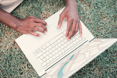 digitally generated image: Digitally generated image of map  against person using laptop on grass Stock Photo