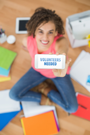 needed: Volunteers needed against smiling businesswoman showing mobile phone in creative office