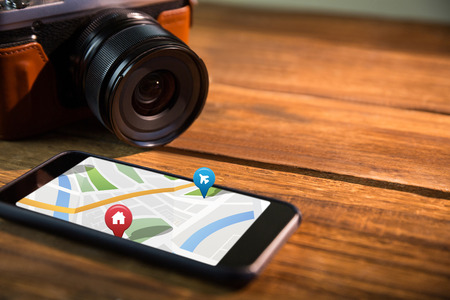 representations: Colorful navigation pointers with various representations on map against smartphone and camera Digital image of colorful navigation pointers with various representations on map