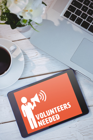 needed: Volunteers needed against tablet and laptop on table