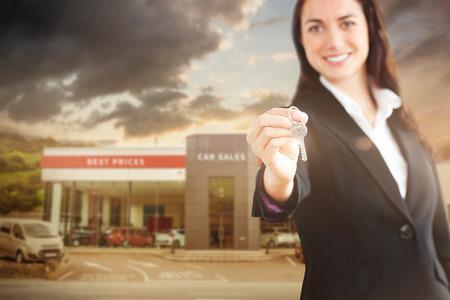 Smiling businesswoman holding a key against car workshop building photo