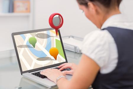 using laptop: Close-up of navigation marker against business worker using laptop at desk