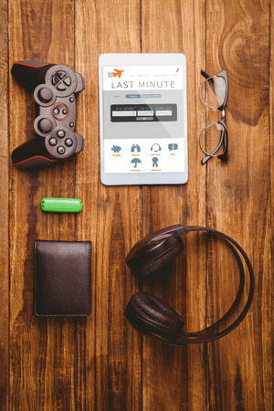 booked: Tablet and glasses next to joystick music headphone and wallet  against holidays booking app