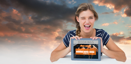 booked: Woman showing tablet pc  against blue and orange sky with clouds