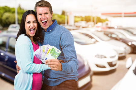 Excited couple holding money against view of row new car