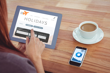over the shoulder view: Over shoulder view of hipster woman using tablet against holidays booking app Stock Photo