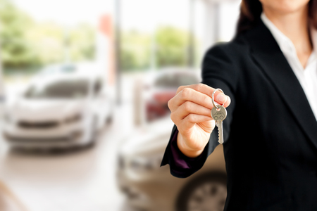 Close up of a confident businesswoman holding a key against view of row new car photo