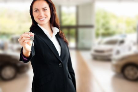 Smiling businesswoman holding a key against view of row new car photo