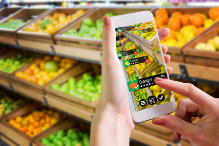 Hand holding smartphone against vegetable shelf at the supermarket Stock Photo