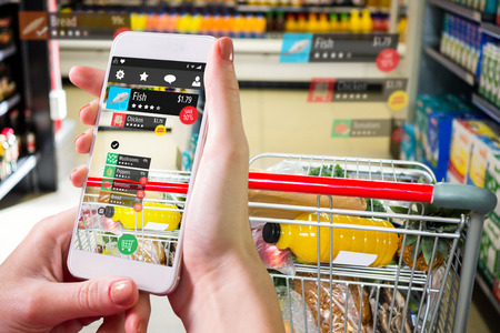 mobile phone screen: Hand holding smartphone against view of filled shopping cart Stock Photo