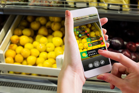 mobile phone screen: Hand holding smartphone against vegetable shelf at the supermarket Stock Photo