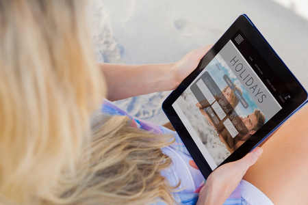 booked: Woman sitting on beach in deck chair using tablet pc against holidays booking app Stock Photo