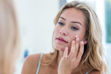 Mujer bonita sonriente que aplica la crema en su cara en el baño