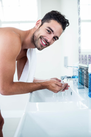 washing face: Man washing his face in sink in bathroom Stock Photo