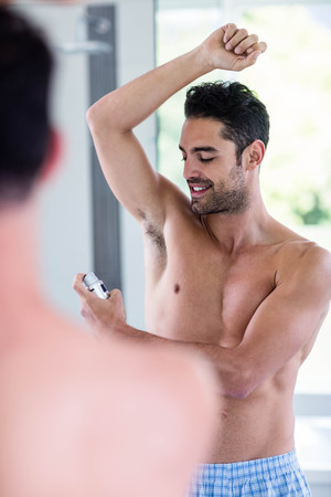 deodorant: Handsome shirtless man putting deodorant in the bathroom