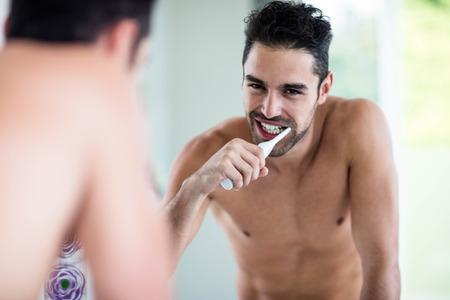 adult brushing teeth: Portrait of a handsome man brushing teeth in the bathroom