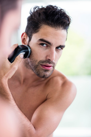 bath towel man: Handsome man shaving in the mirror in the bathroom