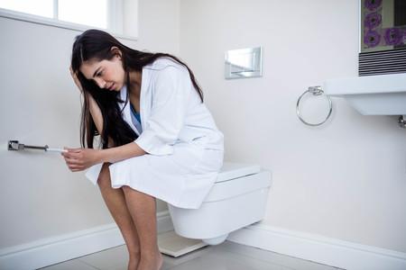prueba de embarazo: Infeliz mujer joven mirando a su prueba de embarazo en el baño