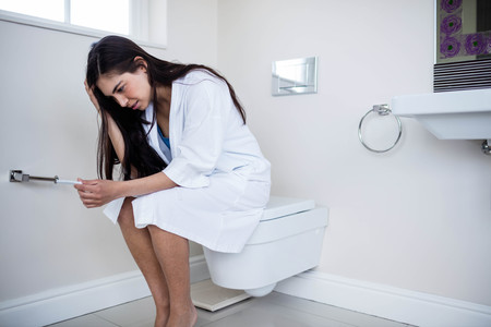 conceive: Unhappy young woman looking at her pregnancy test in toilet Stock Photo