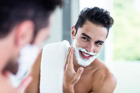 ハンサムな男性の浴室で彼のひげを剃る