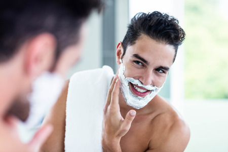 young adult man: Handsome man shaving his beard in bathroom