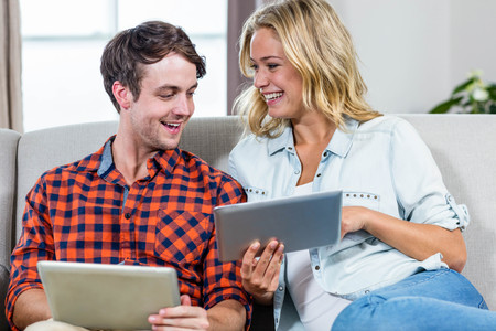 couch: Couple using tablet computers on the couch Stock Photo