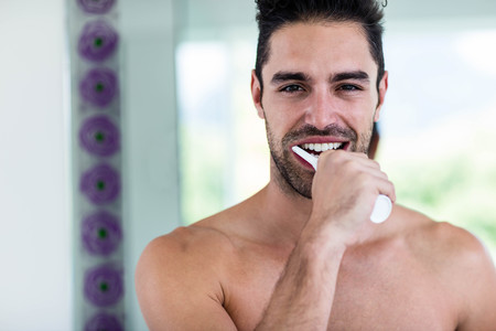 Handsome man brushing his teeth in bathroom Stock Photo