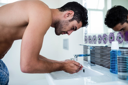 washing face: Handsome man washing his face in bathroom Stock Photo