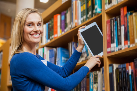 tidying: Female student tidying a tablet in a bookshelf at the university Stock Photo