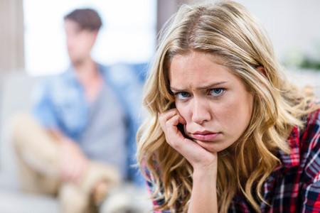 sulking: Upset girlfriend sulking her boyfriend in the living room Stock Photo