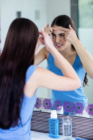 irritation: Unhappy woman with skin irritation cleaning her face at home Stock Photo