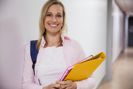 Happy female student walking in the hallway at the university Stock Photo