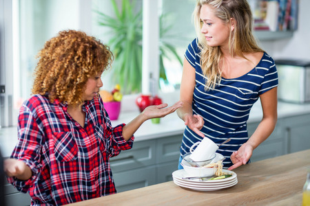 household tasks: Upset woman showing dirty dishes to friend in kitchen