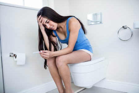 test result: Anxious brunette waiting pregnancy test result in toilet